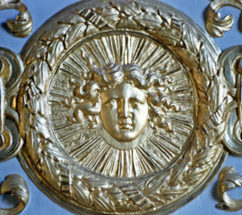 the face of Louis XIV as the Sun King as a gold medallion