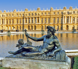 Reclining statue of a god in front of a pond at Versailles, photo by Virginia Ives